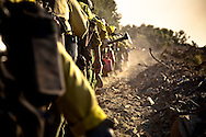 The Groveland Hotshots march in single file toward the safe zone after clearing a fire break in preparation for controlled burning.