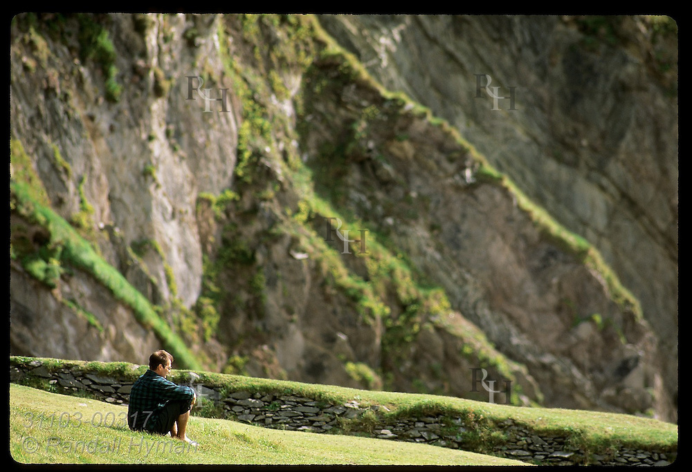 Man sits on grassy slope at tip of Dingle Peninsula with the rocky cliffs of Coumeenole Beach behind him; Ireland.