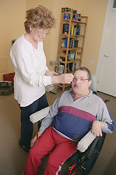 Carer helping to feed man with Cerebral Palsy,