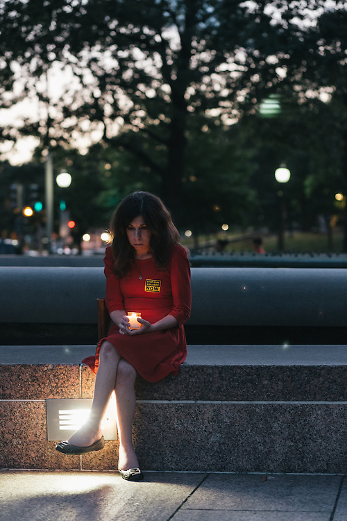 WASHINGTON, DC - SEPTEMBER 16:  Nichole Goble of Washington, D.C. holds a candle to remember victims of gun violence during a vigil at Freedom Plaza in Washington, D.C. on Sept. 16, 2013. The vigil, during which organizers called for stricter gun laws, was in remembrance of the more than 10 killed in a shooting at the Navy Yard earlier in the day.   (Photo by Greg Kahn/Getty Images)