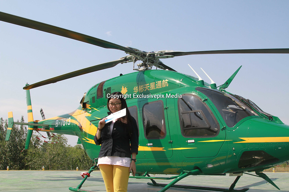 BEIJING, CHINA - MAY 15: (CHINA OUT) <br /> <br /> Can't get a cab in Beijing? No problem as dial-a-chopper takes off and 10,000 sign up for a ride<br /> <br /> Commuters facing packed trains and gridlocked roads in Beijing now have another travel option - after China launched a dial-a-chopper service. <br /> The helicopter hailing scheme has already proved a hit in China's congestion-hit capital with more than 10,000 people signing up for a ride.<br /> But on the launch weekend, just 100 people managed to hail a ride such was the demand, according to the company behind the project.<br /> <br /> <br /> The 142-mile Beijing-Tianjin round trip in a Bell-429 helicopter cost 3,500 yuan (£360) per person, while the roundtrip to suburban Yanxi Lake cost 1,999 yuan (£206). <br /> The transport initiative was jointly launched by Chinese general aviation operator Reignwood Star Co Ltd and China's biggest taxi hailing platform. <br /> <br /> <br /> Thousands signalled their interest in the service using the Did Kuadi platform. But Lv Gang, Reignwood Star's marketing chief, told Reuters: 'It was a three-day trial run from May 15. <br /> 'So many people signed up for it, but we didn't have the capacity to accommodate them.'<br /> <br /> Helicopter leisure flights are a new concept in China where the military controls most of the airspace. <br /> Reignwood must apply for regulatory approval for tours one day in advance, even though Beijing has simplified flight approval procedures for private aircraft since late 2013.<br /> China is expected to become one of the world's biggest small aviation markets in the next five years as Beijing gradually lifts restrictions on flying at low altitude.<br /> ©Exclusivepix Media