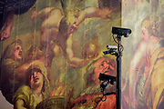 CCTV cameras keep watch on the population, seen in front of a giant construction hoarding in Whitehall, Westminster, London. The illustration is from the Peter Paul Rubens painting 'The Apotheosis of James I' which appears on a ceiling inside the Banqueting House, behind this screen and location of King James' son, Charles' 1st execution.