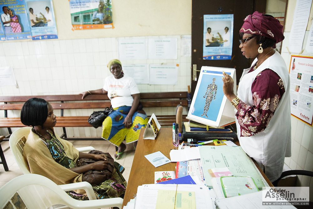 Counselor from UNICEF partner NGO Femme Active Cecile Traore, explains the interaction between drugs and the immune system to Marielle Gnabrayou Digbeto, 28, during a counseling session at the Koumassi general hospital in Abidjan Cote d'Ivoire on Friday July 19, 2013. Marielle is pregnant with her first child and HIV positive. She's taking medicine for eMTCT.