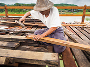 17 SEPTEMBER 2014 - SANGKHLA BURI, KANCHANABURI, THAILAND: A member of the Mon community works on the deck of the Mon Bridge during the bridge's reconstruction. The 2800 foot long (850 meters) Saphan Mon (Mon Bridge) spans the Song Kalia River. It is reportedly second longest wooden bridge in the world. The bridge was severely damaged during heavy rainfall in July 2013 when its 230 foot middle section  (70 meters) collapsed during flooding. Officially known as Uttamanusorn Bridge, the bridge has been used by people in Sangkhla Buri (also known as Sangkhlaburi) for 20 years. The bridge was was conceived by Luang Pho Uttama, the late abbot of of Wat Wang Wiwekaram, and was built by hand by Mon refugees from Myanmar (then Burma). The wooden bridge is one of the leading tourist attractions in Kanchanaburi province. The loss of the bridge has hurt the economy of the Mon community opposite Sangkhla Buri. The repair has taken far longer than expected. Thai Prime Minister General Prayuth Chan-ocha ordered an engineer unit of the Royal Thai Army to help the local Mon population repair the bridge. Local people said they hope the bridge is repaired by the end November, which is when the tourist season starts.    PHOTO BY JACK KURTZ
