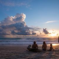 Three travelers watch the sunset from the beach near Banana Beach in Santa Teresa, Costa Rica.