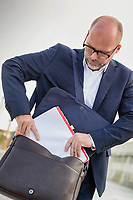 Portrait of mature businessman putting paperwork on his bag