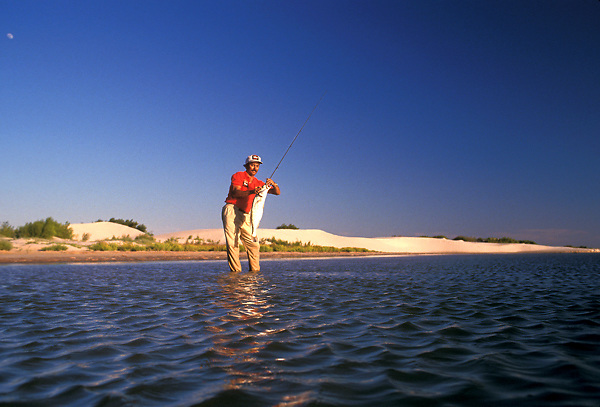 Stock photo of a man wading in the bay and pulling up a freshly caught fish