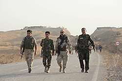 20/10/2016. Bashiqa, Iraq. Four Kurdish peshmerga fighters advance along a road at the beginning of a large offensive to retake the Bashiqa area, and eventually Mosul, from Islamic State militants today (20/10/2016).<br />