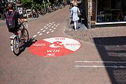 Een man fietst door waar het voetgangersgebied begint. In Utrecht worden fietsers gewezen op een andere route. Vanaf 1 mei mogen fietsers gedurende het grootste deel van de dag niet meer door een deel van het centrum fietsen. Het voetgangersgebied is fors uitgebreid.<br /> <br /> A big painted sign on the road suggest cyclists another route to ride at the city center in Utrecht. A part of the center is closed for cyclists for the main part of the day.