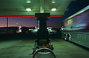 A band tour bus with horse and sea artwork parks at a petrol filling station in early evening at Mojave, California, USA