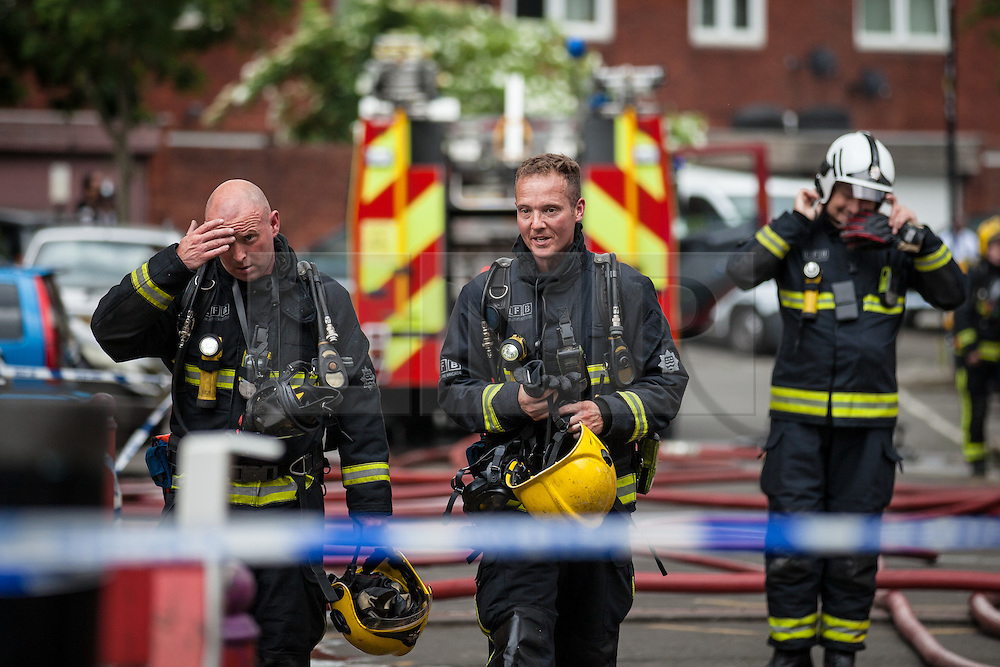 © Licensed to London News Pictures. 11/06/2016. London, UK. Fire crews and paramedics at work after a large fire broke out in a tower block on Canterbury Crescent in Brixton, south London. Plumes of smoke could be seen from across south London, and some on Twitter also reported hearing an explosion. Photo credit: Rob Pinney/LNP
