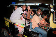 A happy overcrowded family in an auto rickshaws, India, Kerala, a state on the tropical coast of south west India