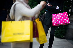 © Licensed to London News Pictures.17/12/2013. London, UK. Shoppers carry shopping bags on Oxford Street only a week before Christmas.Photo credit : Peter Kollanyi/LNP