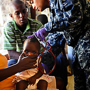 100125-N-5345W-267.GRAND GOAVE, Haiti (Jan. 25, 2010) .Hospital Corpsman 1st class Vilma Bauer, assigned to the amphibious dock landing ship USS Fort McHenry (LSD 43), examines a Haitian infant as her family looks on while seeking treatment at the Lifeline Christian Ministries Mission medical clinic in Grand Goave, Haiti. Fort McHenry along with USS Gunston Hall (LSD 44), USS Carter Hall (LSD 50) and the multi-purpose amphibious assault ship USS Bataan (LHD 5) are participating in Operation Unified Response as the Bataan Amphibious Relief Mission by providing military support capabilities to civil authorities to help stabilize and improve the situation in Haiti in the wake of the 7.0 magnitude earthquake that hit the area Jan. 12. (U.S. Navy photo by Mass Communication Specialist 2nd Class Kristopher Wilson/RELEASED)