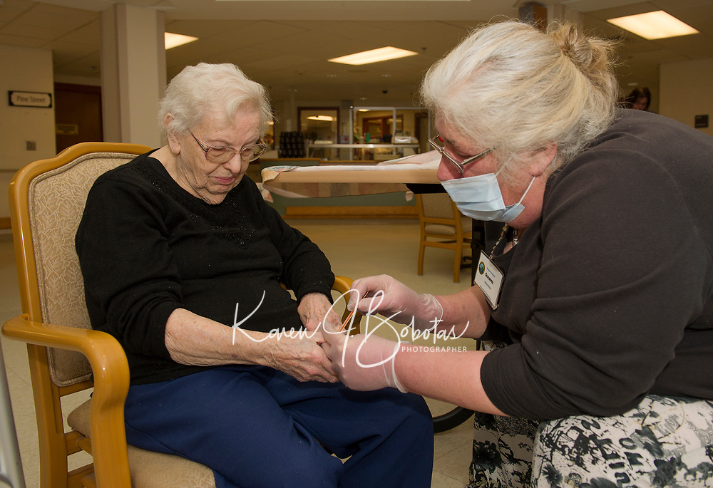 Betty Young gets a manicure by Suzanna, one of the volunteers with Belknap County Nursing Home on Tuesday afternoon.  (Karen Bobotas/for the Laconia Daily Sun)