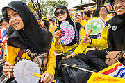 05 DECEMBER 2012 - BANGKOK, THAILAND:  Thai Muslim women wave flags on the Royal Plaza Wednesday while they wait to see Bhumibol Adulyadej, the King of Thailand, before his public audience at the Mukkhadej balcony of the Ananta Samakhom Throne Hall. December 5 is a national holiday. It's also celebrated as Father's Day. Celebrations are being held across the country to mark the birthday of Bhumibol Adulyadej, the King of Thailand.   PHOTO BY JACK KURTZ