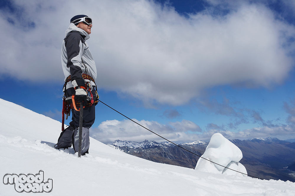 Mountain climber standing on snowy slope with safety line attached