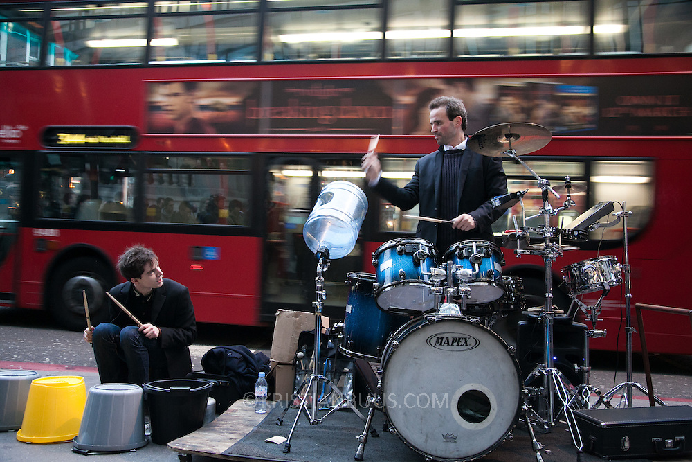 Drummer Oded Kafri, running a project called 'the DruMachine' and partner playing on buckets busk outside Liverpool Street Station at rush hour.