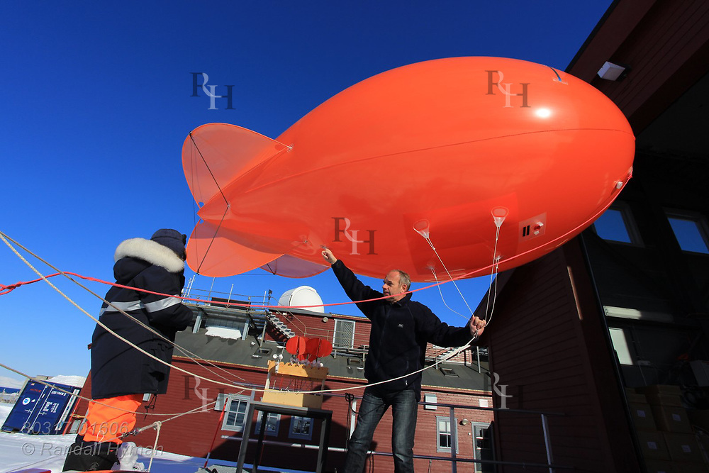 Scientists prepare to launch tethered weather blimp at the French-German AWIPEV research station in the international science village of Ny-Alesund on Spitsbergen island in Kongsfjorden; Svalbard, Norway.