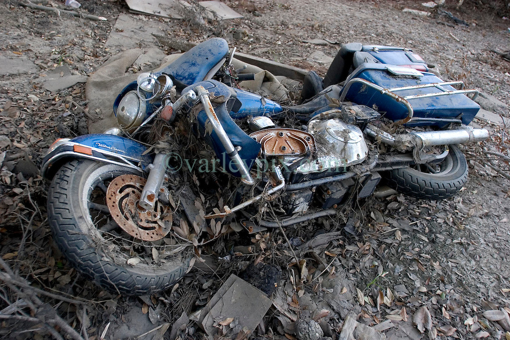 03 Oct, 2005.  New Orleans, Louisiana. Lakeview. Hurricane Katrina aftermath.<br /> The remnants of the lives of ordinary folks, now covered in mud as the flood waters recede. A Harley Davison motorcycle lies trashed in the mud.<br /> Photo; &copy;Charlie Varley/varleypix.com