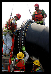 1 June, 2006. Lakeview, New Orleans, Louisiana. First day of hurricane season. Kewit contractors of the Gilbert Southern Group working for the US Army Corps of Engineers work on the $41.5 million Orleans Canal Interim Closure structure. The structure, designed to prevent water build up in the canal during hurricane storm surges is almost complete. Workers tighten massive bolts holding the discharge pipes together. The pumping capacity has yet to match that of pre hurricane Katrina levels, potentially leaving the affluent Lakeview neighbourhood unprotected once again.