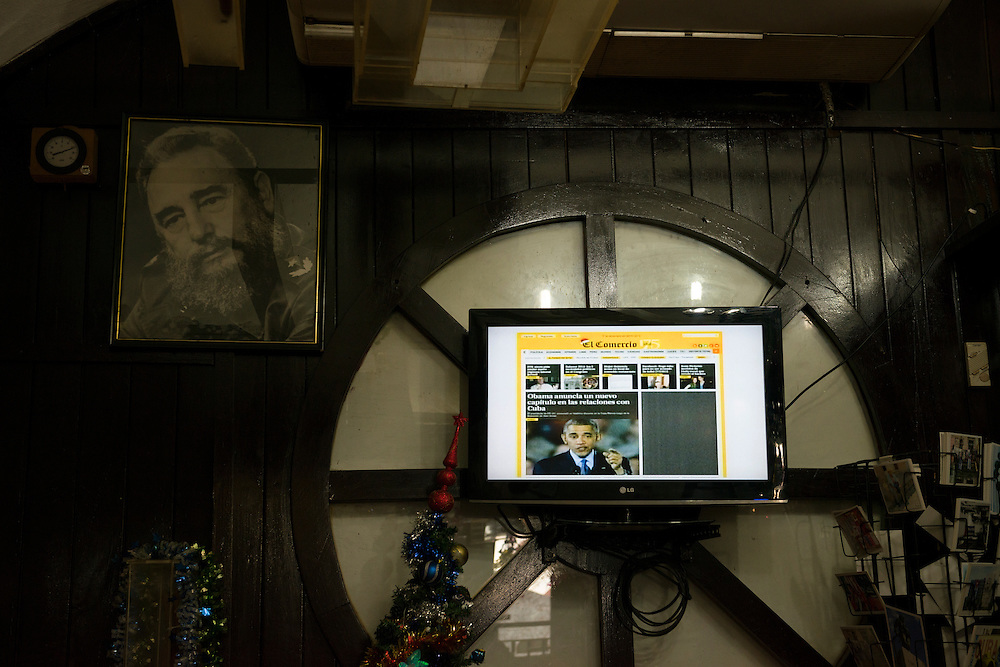Cuban television relays world reaction to the announcement made almost five hours earlier that the U.S. and Cuba would work to restore full diplomatic relations. A portrait of Fidel Castro hangs on the wall. Photo taken at the La Triada shop (home of the world's longest cigar) at Parque Morro-Cabana in Havana, Cuba.