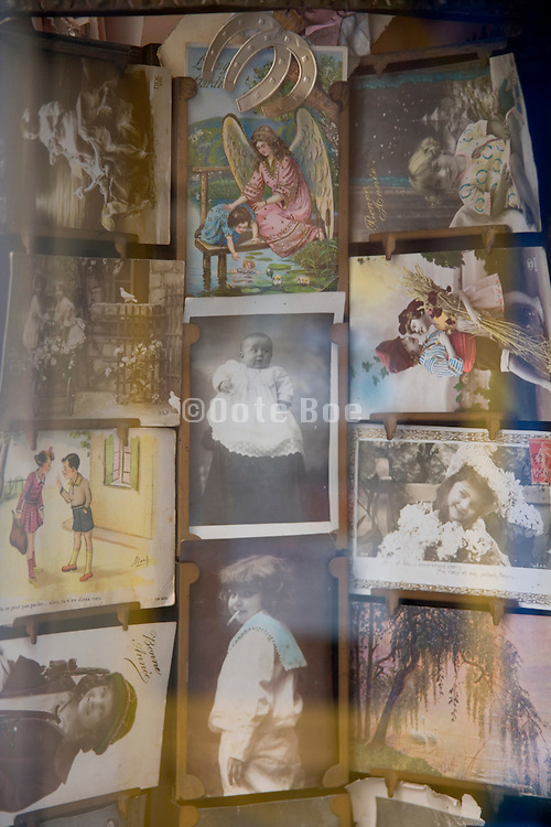 a old postcard stand with various children postcards seen through a window
