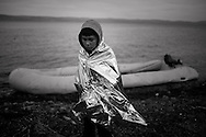 A young boy is wrapped with a warm blanket as refugees and migrants riding a dinghy reach the shores of the Greek island of Lesbos after crossing the Aegean Sea from Turkey on November 16, 2015.