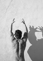 detail of a muscular man's back against a white wall