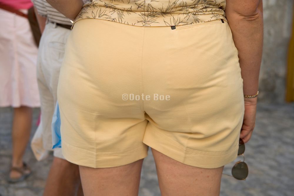 the back of an middle aged woman wearing tight short pants
