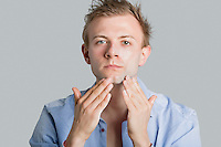 Portrait of young man applying lotion on face over colored background