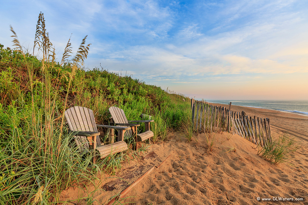 A pair of Adirondack chairs with a great view of Kitty Hawk beach on the Outer Banks.