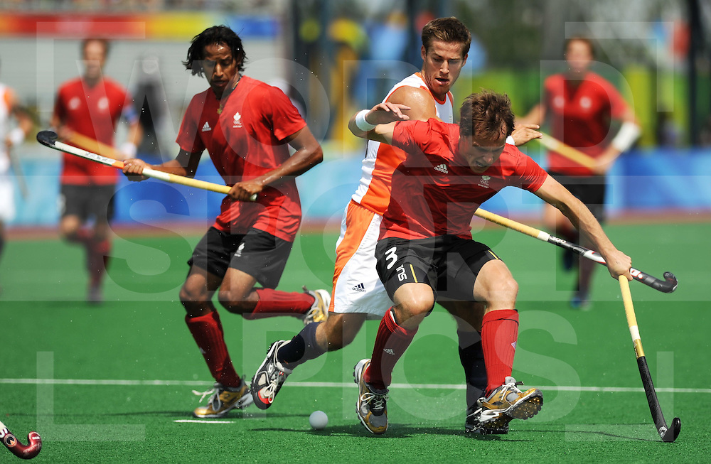 080814 Beijling Chi..Olympic games 2008 Hockey game men...Netherlands - Canada. Jeroen Hertzberger for The Netherlands and in the front Anthony Wright...FFU Press Agency©2008 Frank Uijlenbroek