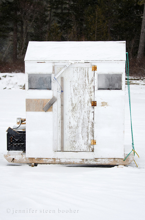 A white-painted ice fishing hut on a frozen lake.