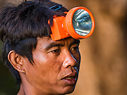 19 JUNE 2016 - DON KHONE, CHAMPASAK, LAOS:  A fisherman with a lantern on his head at Khon Pa Soi Waterfalls, on the east side of Don Khon. It's the smaller of the two waterfalls in Don Khon. Fishermen have constructed an elaborate system of rope bridges over the falls they use to get to the fish traps they set. Fishermen in the area are contending with lower yields and smaller fish, threatening their way of life. The Mekong River is one of the most biodiverse and productive rivers on Earth. It is a global hotspot for freshwater fishes: over 1,000 species have been recorded there, second only to the Amazon. The Mekong River is also the most productive inland fishery in the world. The total harvest of fish from the Mekong is approximately 2.5 million metric tons per year. By some estimates the harvest in the Tonle Sap (in Cambodia) had doubled from 1940 to 1995, but the number of people fishing the in the lake has quadrupled, so the harvest per person is cut in half. There is evidence of over fishing in the Mekong - populations of large fish have shrunk and fishermen are bringing in smaller and smaller fish.    PHOTO BY JACK KURTZ
