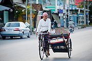 """Sept. 25, 2009 -- PATTANI, THAILAND: A Muslim man peddles his pedicab on a street in Pattani, Thailand. Thailand's three southern most provinces; Yala, Pattani and Narathiwat are often called """"restive"""" and a decades long Muslim insurgency has gained traction recently. Nearly 4,000 people have been killed since 2004. The three southern provinces are under emergency control and there are more than 60,000 Thai military, police and paramilitary militia forces trying to keep the peace battling insurgents who favor car bombs and assassination.  Photo by Jack Kurtz / ZUMA Press"""