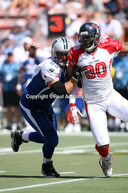 HONOLULU, HI - FEBRUARY 08: NFC All-Stars offensive tackle Jordan Gross #69 of the Carolina Panthers blocks AFC All-Stars defensive end Mario Williams #90 of the Houston Texans in the 2009 NFL Pro Bowl at Aloha Stadium on February 8, 2009 in Honolulu, Hawaii. The NFC defeated the AFC 30-21. ©Paul Anthony Spinelli *** Local Caption *** Jordan Gross;Mario Williams