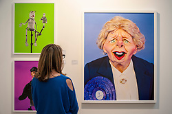 "© Licensed to London News Pictures. 22/04/2015. Piccadilly, London. A woman looks at works by Andrew Bruce and Anna Fox, entitled ""Spitting"", based on the Spitting Image satirical TV show, at the press review look at items on display at the 30th London Original Print Fair, Europe's largest works–on–paper event, which takes place at the Royal Academy of Arts from 23 to 26 April 2015.  On display are works from all periods of printmaking, from the earliest woodcuts of Dürer, to the latest editions by contemporary masters. Photo credit : Stephen Chung/LNP"