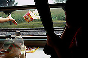A passenger on a train throws the remains of her instant noodles out the window. Anhui, China, 2007