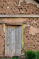 Abandoned & boarded up building, door and adobe wall detail; Gardner, CO