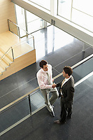Businessmen shaking hands on Mezzanine elevated view
