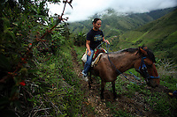 A woman rides a horse along a mountain trail in a coca-growing region in a remote area of the southern Colombian state of Nariño, on Thursday, June 21, 2007. (Photo/Scott Dalton)