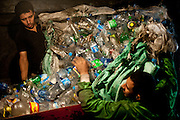 Moussa Zikri, left, and his brother Samaan work at their plastic bottle shredder in the basement of their family home, grinding heaps of plastic bottles into chips.