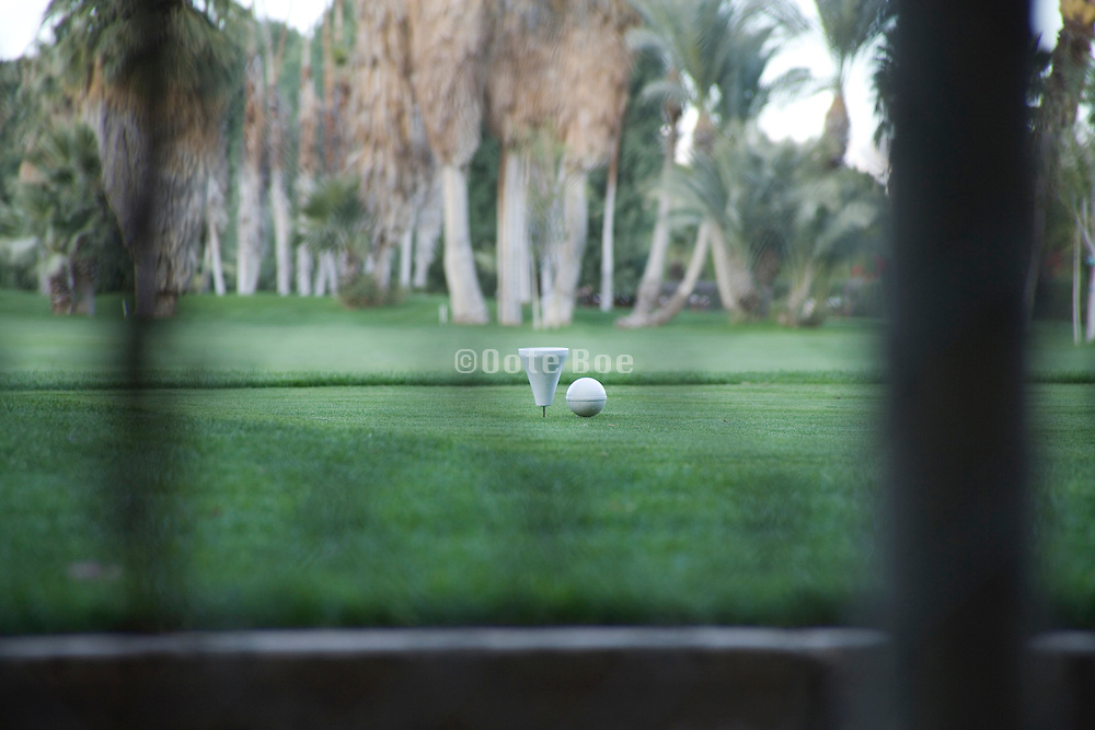 golf ball and tee seen from behind a fence