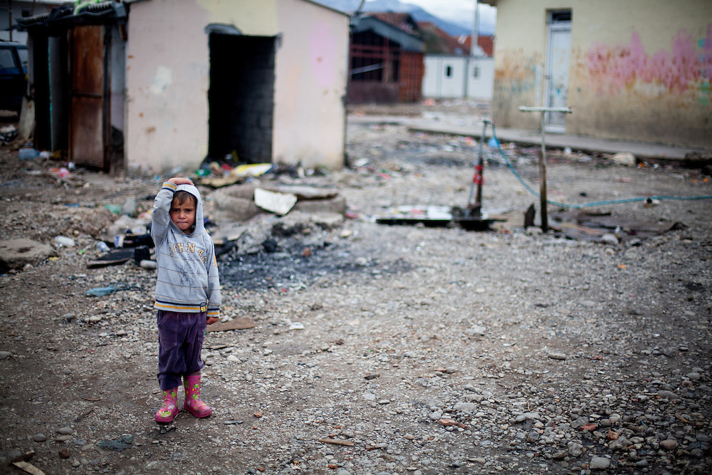 A child standing on the area of Konik Camp located in the suburbs of the city of Podgorica, Montenegro. A huge fire in 2012 detroyed a big part of the refugee camp and many of the inhabitants are living in containers. The housing pictured belongs still to the part with old housing facilities.