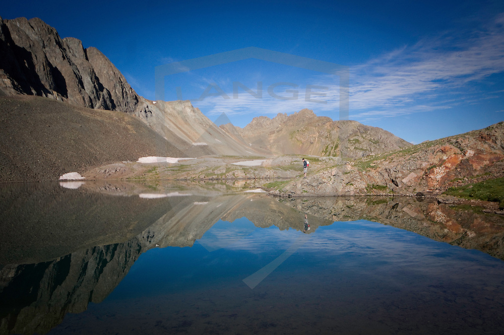 hiker on lakeside with reflection and mountain reflections, sloane lake, american basin, san juan mountains, silverton, colorado.