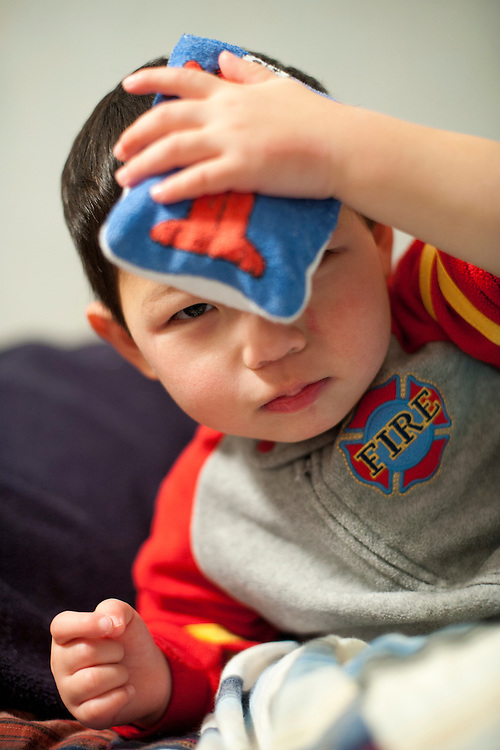 """After bumping his head earlier during the evening, Holden Miller, 2, holds an """"Elmo"""" ice pack over a sizable """"goose egg"""" on his forehead at the Miller/Stue home in Madison, Wis., on Dec. 15, 2009."""