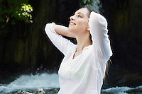 Young woman pulling back hair by river in forest side view