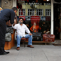 A shop keeper gives a passerby a light in Istanbul, Turkey.
