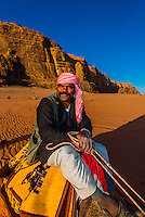 Bedouin man riding a camel in the Arabian Desert, Wadi Rum, Jordan.